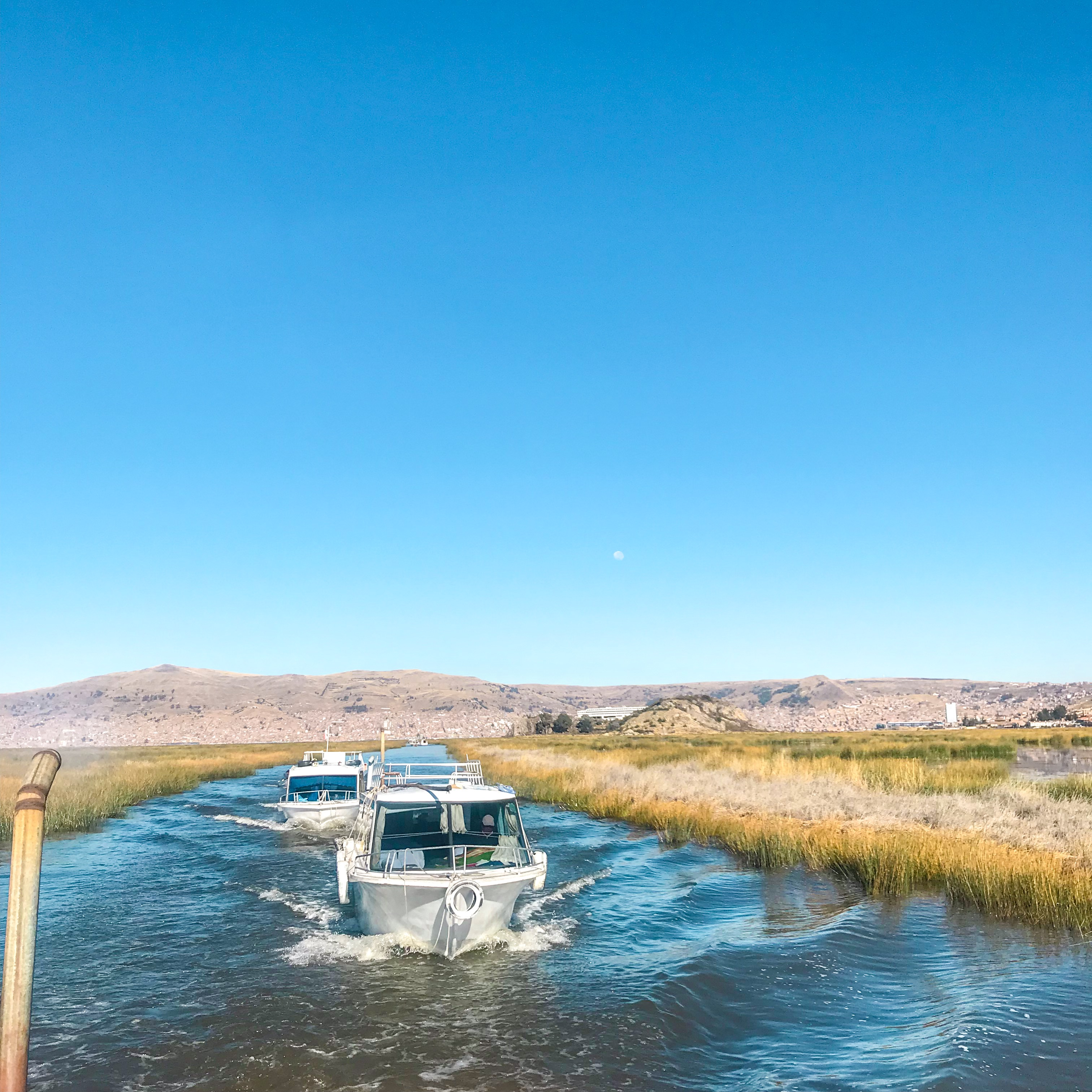 Boat tours on Lake Titicaca, Peru, taking tourists to the Uros Floating Islands through the reeds.